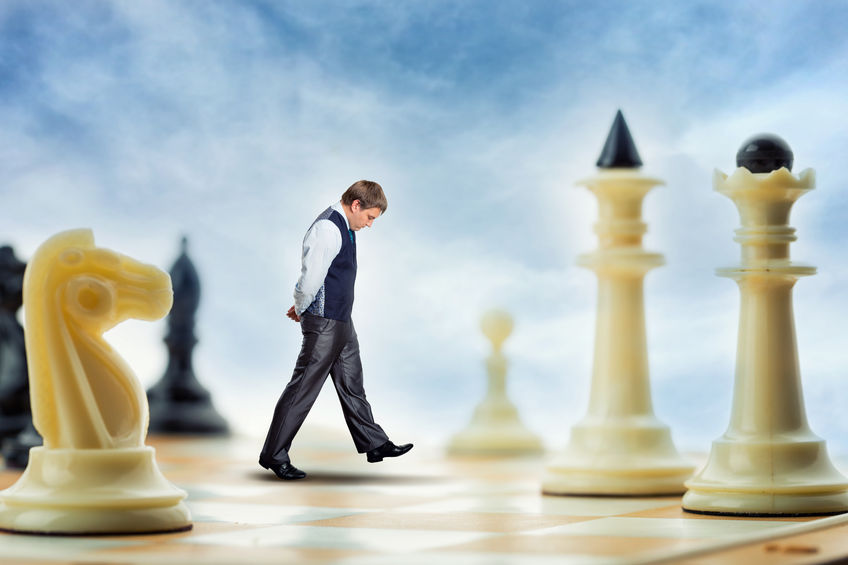 56897881 - businessman is walking on the chess board thinking